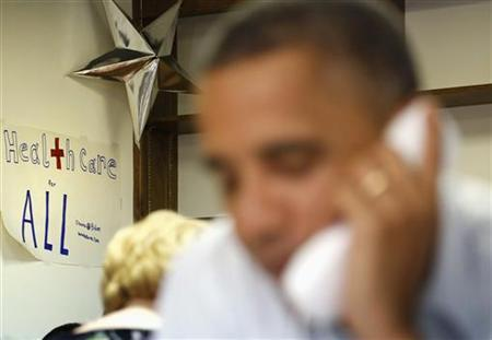 A sign reading ''Healthcare for All'' decorates the wall behind U.S. President Barack Obama as he makes thank you calls to volunteers from his campaign office in Williamsburg, Virginia, October 14, 2012.<br /> Credit: Reuters/Jonathan Ernst