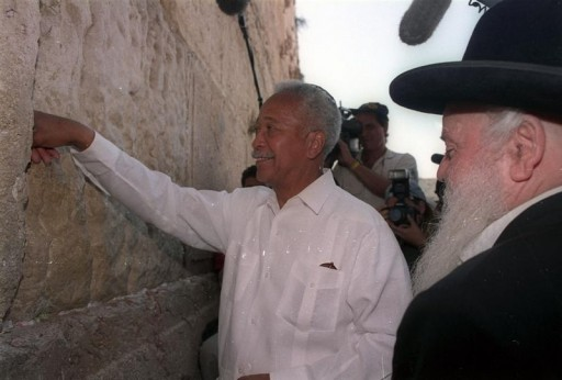 FILE - New York Mayor David Dinkins, accompanied by a rabbi, inserts a prayer on a piece of paper in the Wailing Wall on July 8, 1993, the Jewish people's holiest site inside Jerusalem's walled Old City. Reuters/Havakuk Levison
