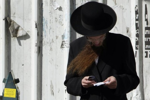 FILE - An ultra Orthodox Jewish man uses his cellular phone along a street in Bnei Brak, near Tel Aviv May 3, 2011.  Reuters
