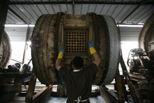 FILE - An ultra-Orthodox Jewish worker operates a wooden barrel used to wash cowhides at a Judaica factory which makes ritual Tefillin in Moshav Kommemiyut, near Kiryat Gat March 4, 2012.  Reuters