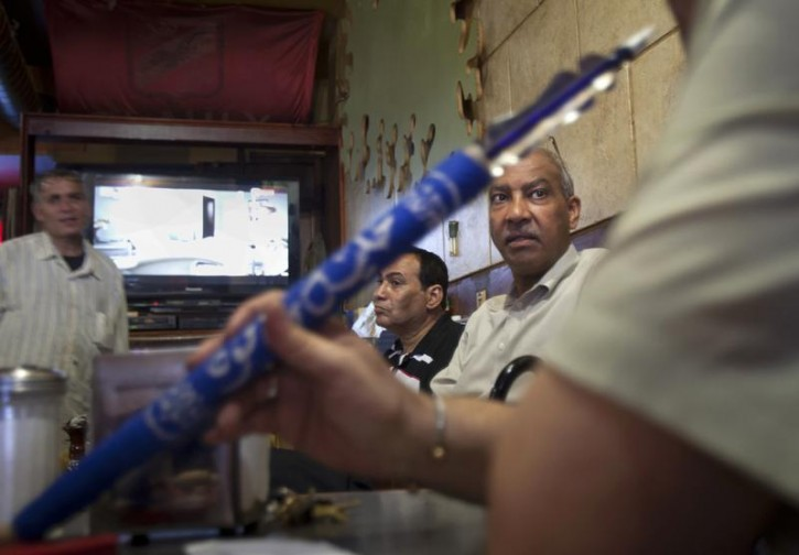 Egyptians sit in a Hookah Bar while watching and discussing the news in Egypt in the Queens borough of New York, July 3, 2013. Egypt's armed forces overthrew elected Islamist President Mursi on Wednesday and announced a political transition with the support of a wide range of political, religious and youth leaders.  REUTERS/Carlo Allegri