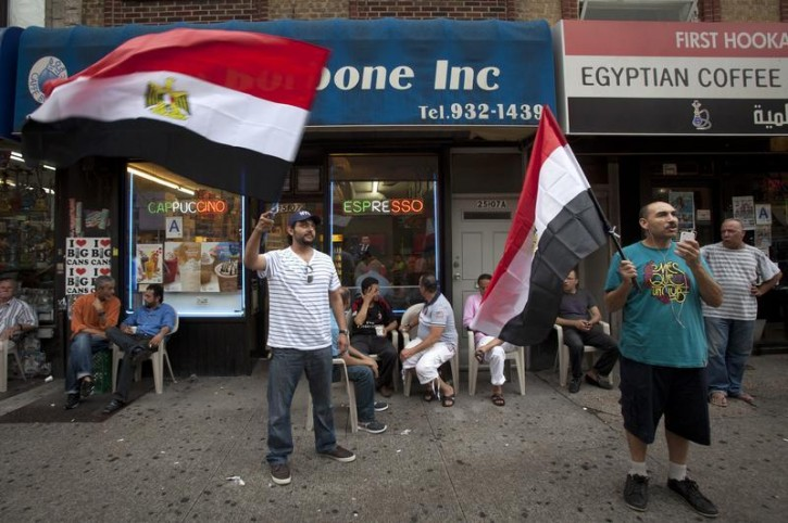 Men wave Egyptian flags on the street in the Queens borough of New York, July 3, 2013. Egypt's armed forces overthrew elected Islamist President Mursi on Wednesday and announced a political transition with the support of a wide range of political, religious and youth leaders.   REUTERS/Carlo Allegri