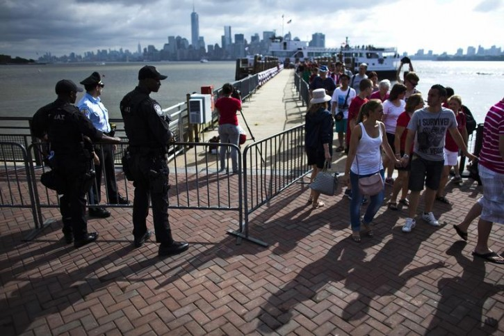 A SWAT team member stands guard while people arrive to visit the Statue of Liberty and Liberty Island during its reopening to the public in New York July 4, 2013. The Statue of Liberty and Liberty Island opens to the public for the first time since Hurricane Sandy made landfall on October 29, 2012.  REUTERS/Eduardo Munoz