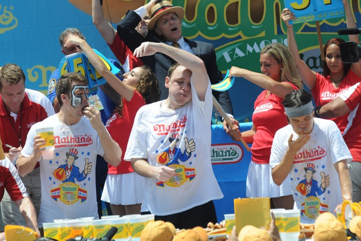 Competitive eaters Tim Janus (L), Joey Chestnut (C) and Matt Stonie (R) eat hot dogs as they participate in the Nathan's Famous Fourth of July International Hot-dog Eating contest in the Coney Island area of New York City, New York, 04 July 2013. Chestnut set a record for eating 69 hotdogs and buns as he went on to his seventh straight contest.  EPA/KEITH BEDFORD