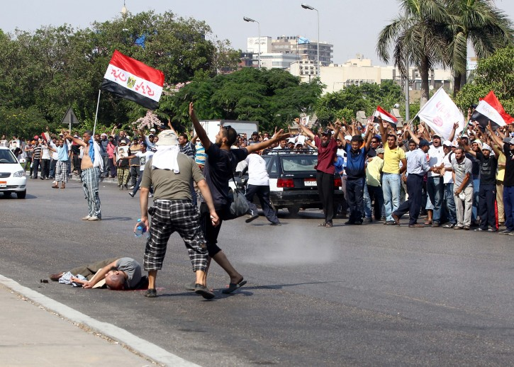 Supporters of the ousted Egyptian President Mohamed Morsi try to reach to a fellow who was shot during the clashes next the headquarters of the Republican Guard, in Cairo, Egypt, 05 July 2013. According to reports, shots were fired during a gathering of supporters of ousted Egyptian President Mohamed Morsi in Cairo, leaving at least one man killed. Backers of Morsi on 05 July staged huge protests across Egypt, where fighting between the Islamist leader's supporters and opponents have raised fears of deadly street violence in the Arab world?s most populous country.  EPA/KHALED ELFIQI