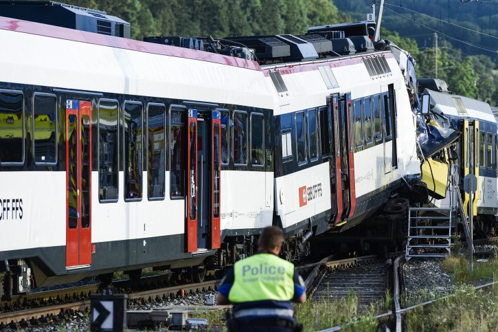 A policeman inspects the scene of a train collision in Granges-pres-Marnand in Western Switzerland, 29 July 2013. Several passengers are reported injured in the accident that caused disruption of traffics to the track section between Moudon and Payerne.  EPA/LAURENT GILLIERON