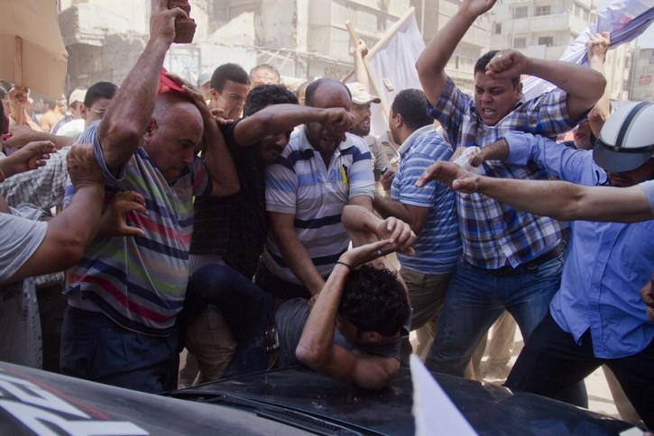An Egyptian opposition protester is beaten by supporters of former Egyptian president Mohammed Morsi, as a man raises a brick overhead, in downtown Damietta, Egypt, on Wednesday. (Hamada Elrasam / AP)
