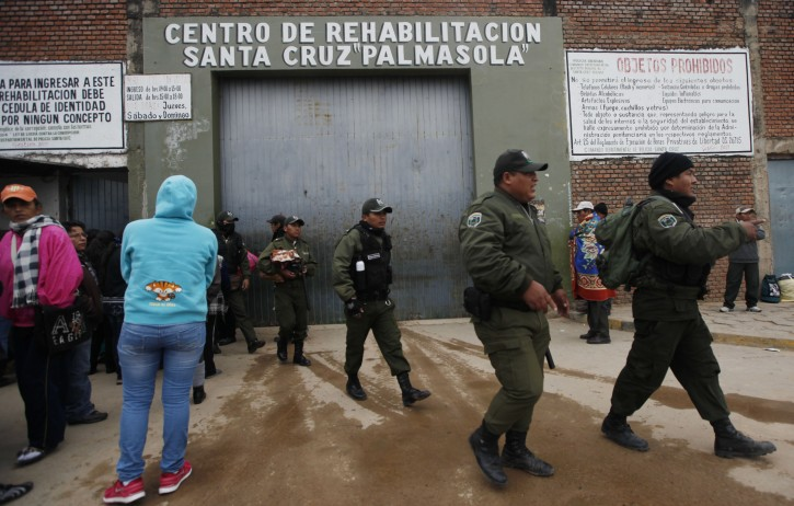 Police walk outside Palmasola prison one day after a deadly riot as prisoners' families wait for information about their loved ones in Santa Cruz, Bolivia, Saturday, Aug. 24, 2013. A battle among rival gangs in this prison in Bolivia's eastern lowlands Friday left at least 30 people dead, many burned to death, as witnesses said inmates used propane gas tanks as flamethrowers. (AP Photo/Juan Karita)