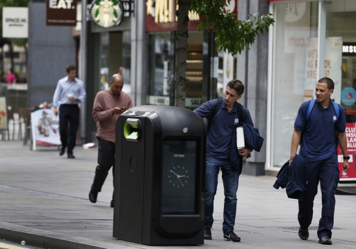 A youth uses a trash bin in central London, Monday, Aug. 12, 2013. Officials say that an advertising firm must immediately stop using its network of high-tech trash cans, like this one, to track people walking through London's financial district. The City of London Corporation says it has demanded Renew pull the plug on the program, which measures the Wi-Fi signals emitted by smartphones to follow commuters as they pass the garbage cans. (AP Photo/Lefteris Pitarakis)