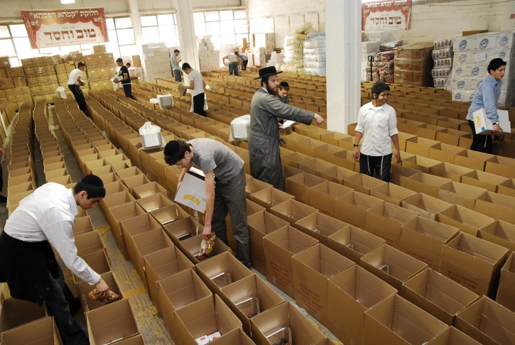 In this Undated file photo 30 year old Yakov Shisha founder of Tov Vchesed standing center directing his volunteers with the package packing