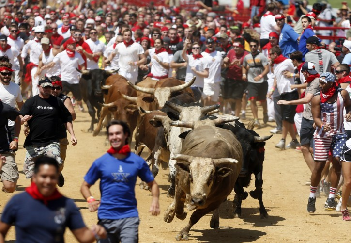 Runners clear out in front of the bulls during The Great Bull Run event at the Virginia Motorsports Park in Dinwiddie, Va., on Saturday, Aug., 24, 2013. (AP Photo/Richmond Times-Dispatch, Joe Mahoney)