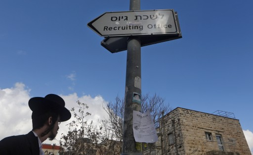 A Ultra Orthodox Jewish man walking next to a sign pointing at the Israeli Army recruiting office in Jerusalem. EPA/ABIR SULTAN