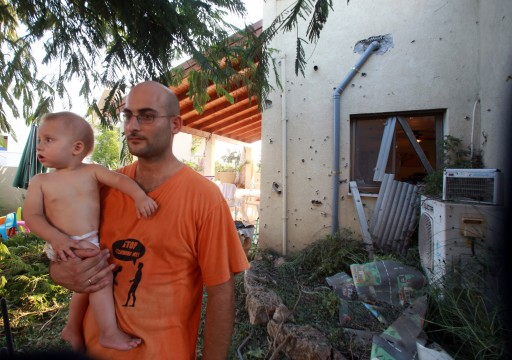An Israeli with his infant son at a house damaged by a rocket reportedly fired from southern Lebanon smashing into the yard of a house in a northern community of Israel, 22 August 2013. EPA/MIRI TZAHI I