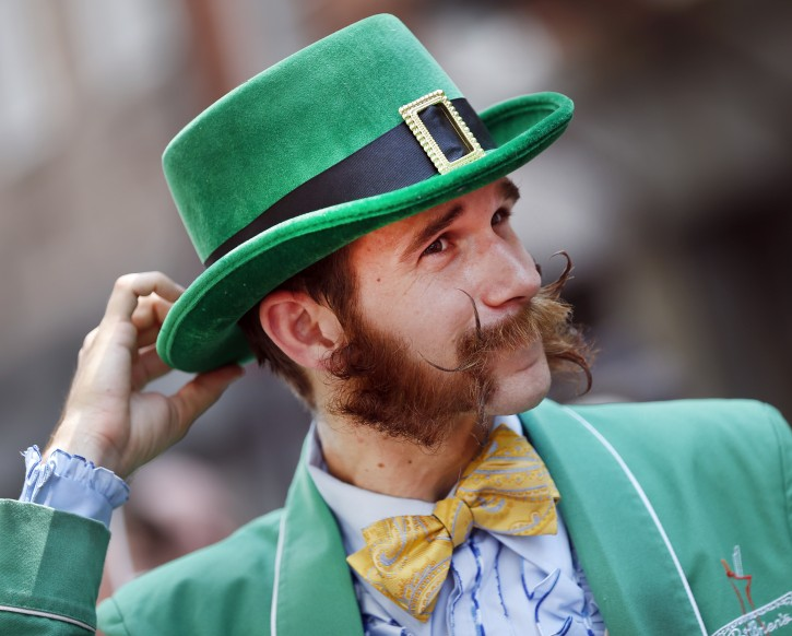 Pierre Dupleix of New Orleans, a bartender at the famed Pat O'Brien's bar in the French Quarter, adjusts his hat while participating in a parade through the French Quarter kicking off the fourth annual Just For Men National Beard and Moustache Championships Saturday, Sept. 7, 2013 in New Orleans. Dupleix said it took him five months to grow his sideburns. Contestants competed in 18 different categories including Dali, full beard natural and sideburns. (AP Photo/Susan Poag)