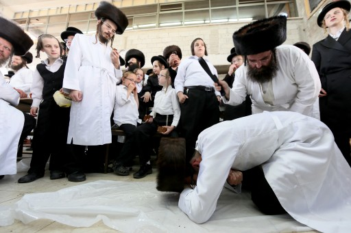 """FILE - An Ultra Orthodox Jewish man of the Hassidic Lelov dynasty whips another ultra orthodox Jewish man with a leather belt as a symbolic punishment for his sins during the traditional """"Malkot"""" ceremony, a few hours before the start of Yom Kippur, the Jewish holy day of Atonement, in a synagogue in the town of Bet Shemesh, outside of Jerusalem. September 25, 2012.  Photo by Nati Shohat / FLASH90"""