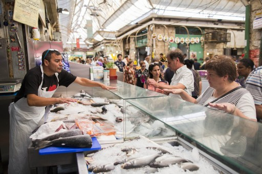 People shop for fish at the Mahane Yehuda market in Jerusalem ahead of Rosh Hashanah, the Jewish New Year which starts at sundown on Monday, September 2, 2013. Photo by Yonatan Sindel/Flash90