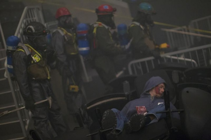 A man, who is acting as a victim with a piece of shrapnel in his chest, lies down in the seats during a mock disaster drill at the Barclays Center in the Brooklyn borough of New York September 13, 2013. The United States Marine Corps and the Fire Department of New York held a simulation of two explosions during a basketball game that utilized chemical and nuclear contaminants.    REUTERS/Carlo Allegri