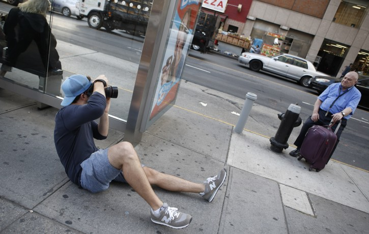 """This Oct. 2, 2013 photo shows photographer Brandon Stanton, creator of the Humans of New York blog, shooting a portrait along East 14th Street in New York.  Stanton's magical blend of portraits and poignant, pithy storytelling has earned HONY more than 2 million followers online.  Now he's putting his work in a book, """"Humans of New York,"""" due out Oct. 15 from St. Martin's Press. (AP Photo/Kathy Willens)"""