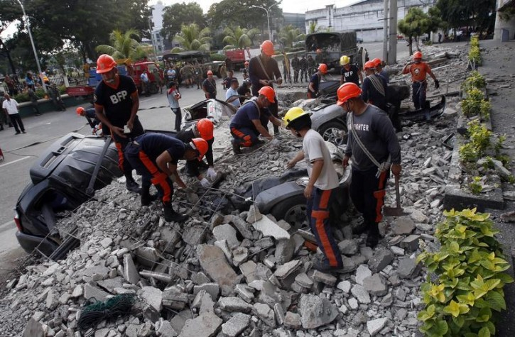 Rescuers clear debris from buried vehicles after an earthquake struck Cebu city, in central Philippines October 15, 2013. A strong earthquake measuring 7.2 struck islands popular with tourists in the Philippines on Tuesday killing at least 20 people, some while praying in a centuries-old church, officials said.   REUTERS/Erik De Castro