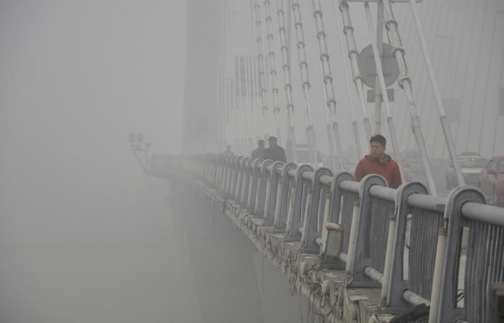 People walk on a bridge during a smoggy day in Jilin, Jilin province, October 21, 2013. Air quality in Chinese cities is of increasing concern to China's stability-obsessed leadership because it plays into popular resentment over political privilege and rising inequality in the world's second-largest economy. REUTERS/Stringer
