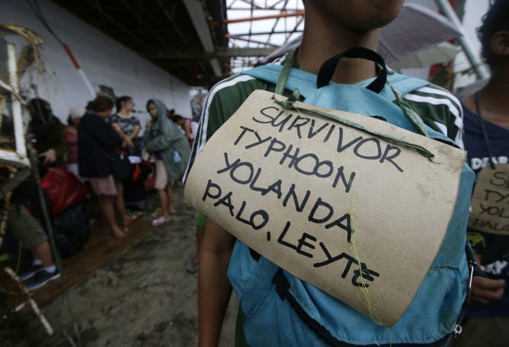 Typhoon survivors hang signs from their necks as they queue up in the hopes of boarding a C-130 military transport plane Tuesday, Nov. 12, 2013, in Tacloban, central Philippines. Thousands of typhoon survivors swarmed the airport on Tuesday seeking a flight out, but only a few hundred made it, leaving behind a shattered, rain-lashed city short of food and water and littered with countless bodies. The typhoon, known as Haiyan elsewhere in Asia but called Yolanda in the Philippines, was likely the deadliest natural disaster to beset this poor Southeast Asian nation. (AP Photo/Bullit Marquez)