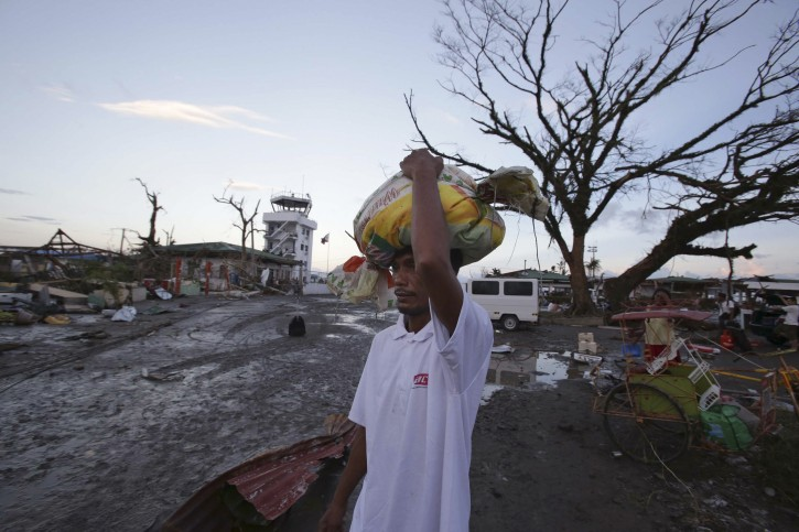 A survivor carries relief goods amongs the devastation after powerful Typhoon Haiyan slammed into Tacloban city, Leyte province central Philippines on Saturday, Nov. 9, 2013. Typhoon Haiyan, one of the most powerful typhoons ever recorded, according to U.S. Navy's Joint Warning Center, slammed into central Philippine provinces Friday leaving a wide swath of destruction and scores of people dead.  (AP Photo/Aaron Favila)