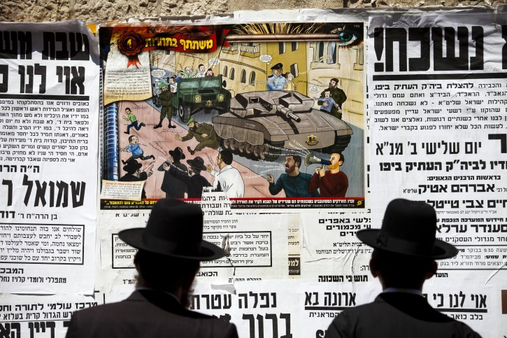 Poster with a cartoon depicting Israeli soldiers pursuing Ultra Orthodox Jewish children, in the Mea Shearim Neighborhood of Jerusalem, Israel, 11 July 2013. EPA FILE/ABIR SULTAN