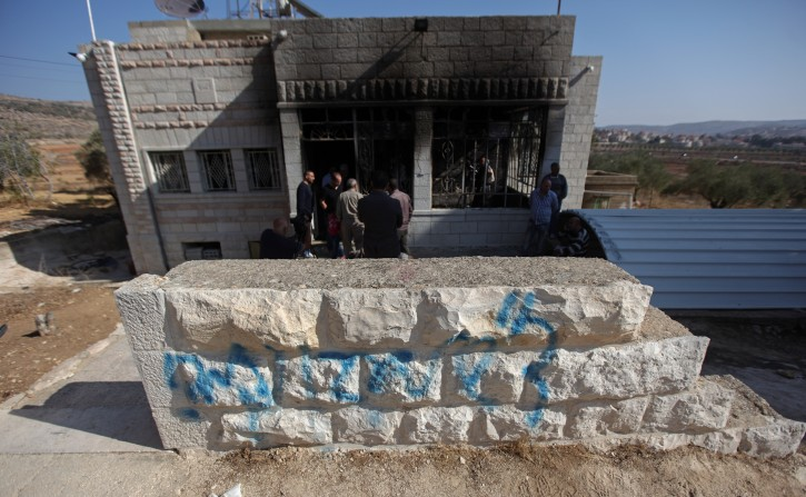 Hebrew graffiti sprayed on a wall reads 'Regards from Eden, Revenge!' in front of a fire-ravaged Palestinian house in the West Bank village of Sinjil, 14 November 2013. EPA/ATEF SAFADI