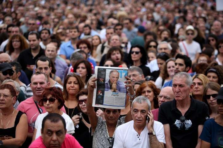 An Israeli woman holds of portrait of late Israeli singer and songwriter Arik Einstein during his funeral ceremony at Rabin's Square in Tel Aviv, Israel, 27 November 2013. Arik Einstein died of a heart failure on 26 November. He was 74. Thousands of Israelis came to pay their last respects to the country's great cultural figure.  EPA/ABIR SULTAN