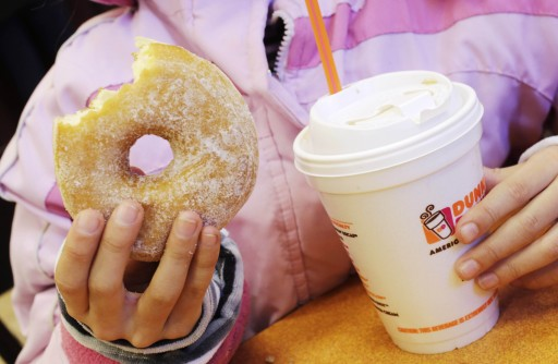FILE - In this Feb. 14, 2013 file photo, a girl holds a beverage, served in a foam cup, and a donut at a Dunkin' Donuts in New York. (AP Photo/Mark Lennihan, File)