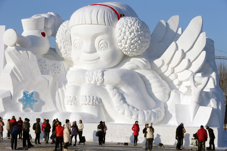 Visitors stand in front of a large snow sculpture at the Sun Island Park during the 26th China Harbin International Snow Sculpture Art Expo in Harbin, Heilongjiang province, China, 20 December 2013. This expo displays many artworks mado of snow at an area of 600,000 sqm.  EPA/WU HONG
