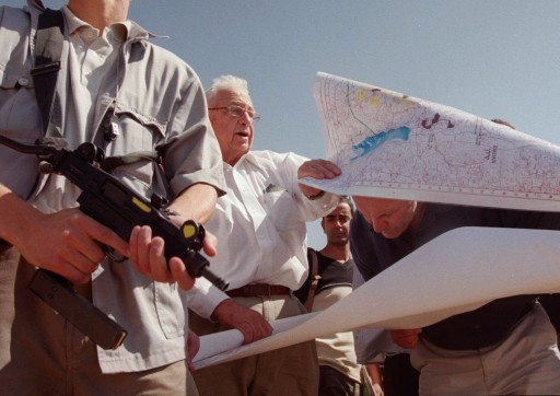 FILE - In this Thursday, Oct. 14, 1999 file photo, Ariel Sharon, center, leader of the opposition Likud party, unfurls maps of Israeli settlements in the West Bank with right-wing Knesset member Hanan Porat, right, during a tour of the West Bank settlement of Har Harasha northwest of Ramallah. Sharon, the hard-charging Israeli general and prime minister who was admired and hated for his battlefield exploits and ambitions to reshape the Middle East, died Saturday, Jan. 11, 2014. The 85-year-old Sharon had been in a coma since a debilitating stroke eight years ago. (AP Photo/Jacqueline Larma, File)