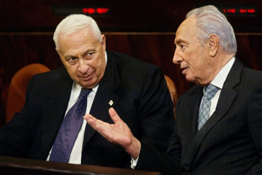 FILE - In this Wednesday, Jan. 12, 2005 file photo, Israeli Prime Minister Ariel Sharon, left, speaks with second vice premier and Labor party leader Shimon Peres prior to a session in the Knesset, Israel's parliament, for the budget vote, in Jerusalem. Sharon, the hard-charging Israeli general and prime minister who was admired and hated for his battlefield exploits and ambitions to reshape the Middle East, died Saturday, Jan. 11, 2014. The 85-year-old Sharon had been in a coma since a debilitating stroke eight years ago.(AP Photo/Oded Balilty, FIle)