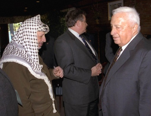 "FILE - In this Oct. 21, 1998 file photo, Israeli Foreign Minister Ariel Sharon, right, stands near but does not look at, or shake hands with, Palestinian leader Yasser Arafat at Wye Plantation, Maryland. Before becoming a candidate, Sharon proudly boasted he had never shaken hands with Arafat, and called the Palestinian leader a ""murderer and a liar"" in an interview with the New Yorker magazine. Sharon, the hard-charging Israeli general and prime minister who was admired and hated for his battlefield exploits and ambitions to reshape the Middle East, died Saturday, Jan. 11, 2014. The 85-year-old Sharon had been in a coma since a debilitating stroke eight years ago. (AP Photo/Israel Government Press Office, File)"