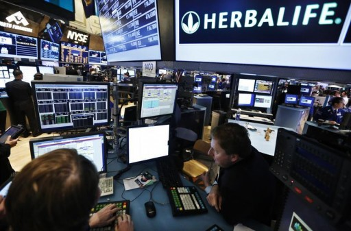 FILE - Traders work at the post that trades Herbalife stock on the floor of the New York Stock Exchange in this January 10, 2013 file photograph.  Reuters