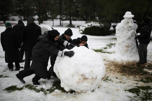 FILE - Ultra-Orthodox Jewish men roll a snowball after a snowstorm at a park during winter in Jerusalem December 12, 2013. Reuters