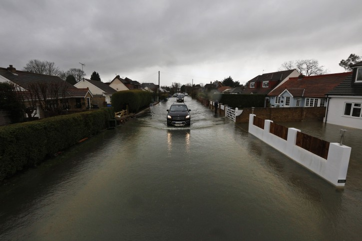 Residents drive through the flooded part of the village of Wraysbury, England, Wednesday, Feb. 12, 2014. Britain's weather service has said climate change is likely linked to a spate of storms and floods battering the country _ the latest of which hit the west coast Wednesday with winds gusting at more than 100 miles (160 kilometers) an hour. (AP Photo/Lefteris Pitarakis)