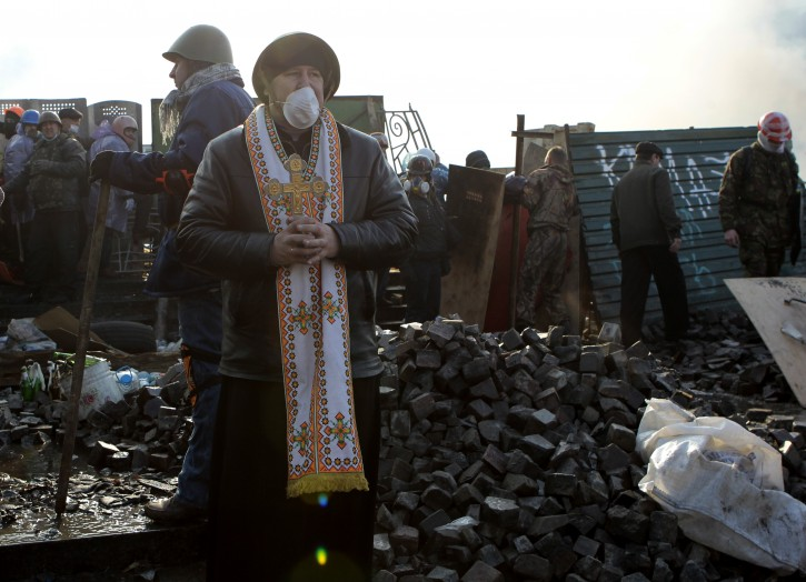 An Orthodox priest stands at the barricades during clashes with riot police in Kiev's Independence Square, the epicenter of the country's current unrest, Kiev, Ukraine, Wednesday, Feb. 19, 2014. The deadly clashes in Ukraine's capital have drawn sharp reactions from Washington, generated talk of possible European Union sanctions and led to a Kremlin statement blaming Europe and the West. (AP Photo/Sergei Chuzavkov)