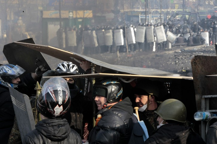 Anti-government protesters protect themselves with shields during clashes with riot police in Kiev's Independence Square, the epicenter of the country's current unrest, Kiev, Ukraine, Wednesday, Feb. 19, 2014. The deadly clashes in Ukraine's capital have drawn sharp reactions from Washington, generated talk of possible European Union sanctions and led to a Kremlin statement blaming Europe and the West. (AP Photo/Sergei Chuzavkov)