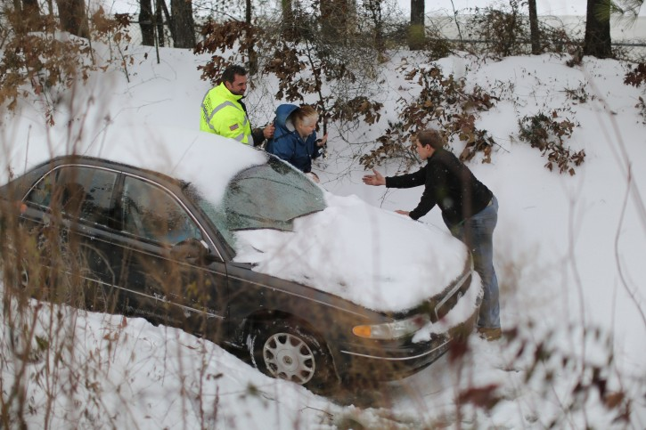 Jacqueline Helton is taken to safety by roadside assistance personnel after her car slid down an embankment on All-American Highway during a winter storm Wednesday, Feb. 12, 2014, in Fayetteville, N.C. Helton was stuck in the embankment for about two hours. (AP Photo/The Fayetteville Observer, Jill Knight)