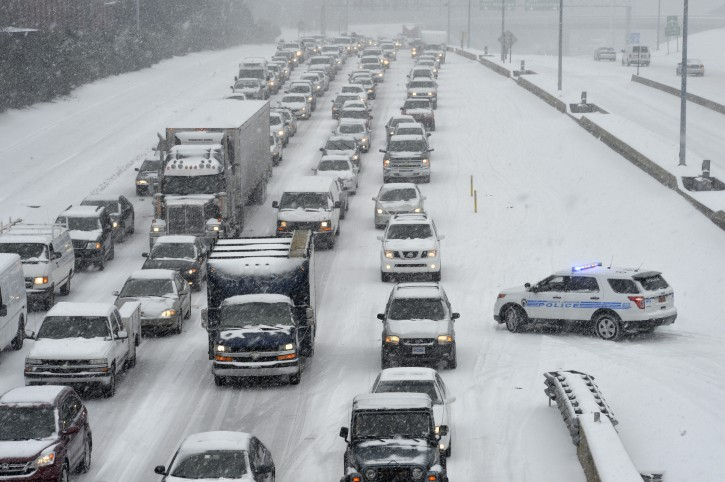 Traffic along Independence Boulevard near Hawthorne Lane crawls along the slick roadway as a winter storm hits   Wednesday, Feb. 12, 2014, in Charlotte, N.C. (AP Photo/The Charlotte Observer, Davie Hinshaw)