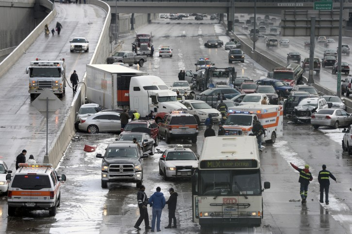 Emergency workers respond to a massive pileup accident on Interstate 25 in Denver, Saturday, March 1, 2014. Authorities say one person was killed and 30 others were injured in the giant pileup. (AP Photo/The Denver Post, Kathryn Scott Osler)