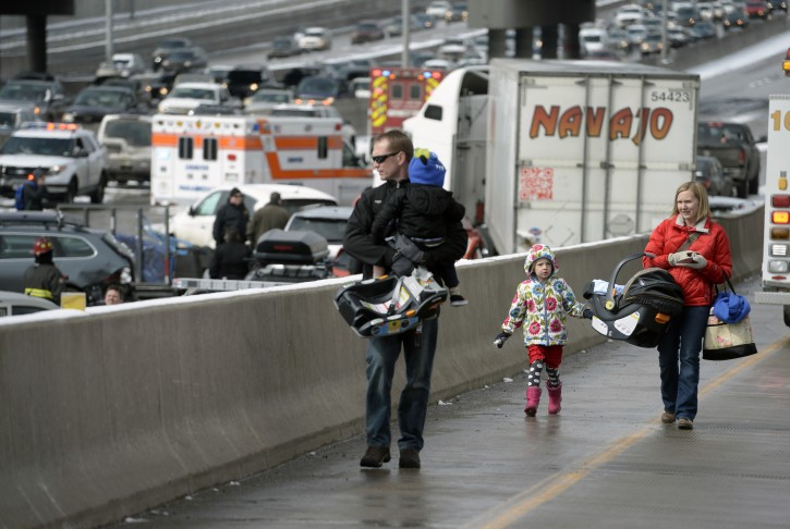 A family involved a massive pileup accident on Interstate 25, who declined to give their names, walk up the on ramp that leads from South Washington Street onto Interstate 25, in Denver, Saturday, March 1, 2014.  Authorities say one person was killed and 30 others were injured in the giant pileup. (AP Photo/The Denver Post, Kathryn Scott Osler)