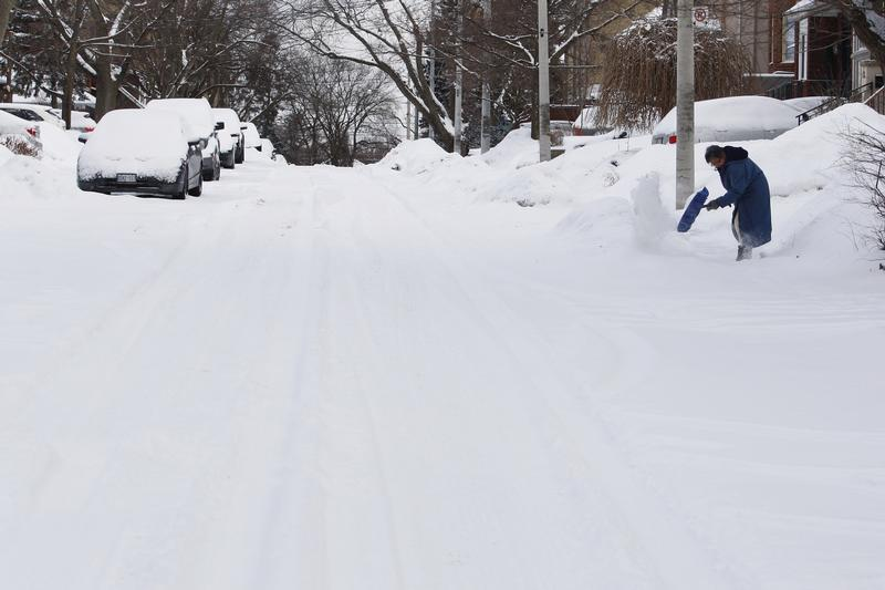 resident clears snow following an overnight snow storm in Toronto