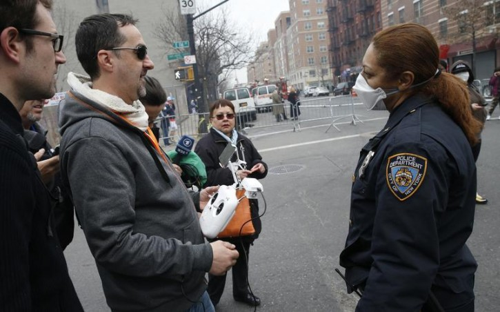 A New York City police officer (R) tells Brian Wilson to land the drone that he was flying over the scene where two buildings were destroyed in an explosion, in the East Harlem section in New York City, March 12, 2014. Two New York buildings collapsed on Wednesday in an explosion believed to be caused by a gas leak, killing two people, injuring at least 22, and setting off a search for more feared trapped in the debris, officials said.   REUTERS/Mike Segar