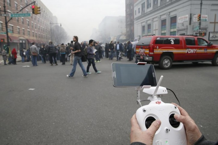 A camera drone flown by Brian Wilson flies near the scene where two buildings were destroyed in an explosion, in the East Harlem section in New York City, March 12, 2014. Two New York buildings collapsed on Wednesday in an explosion believed to be caused by a gas leak, killing two people, injuring at least 22, and setting off a search for more feared trapped in the debris, officials said.   REUTERS/Mike Segar