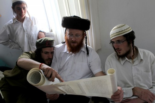 FILE - Jewish settlers, one in the costume of a soldier, read from the Book of Ester, or the 'Megilla' as they celebrate the Jewish holiday of Purim in the northern West Bank settlement called Havat Gilad, on 20 March 2011. EPA