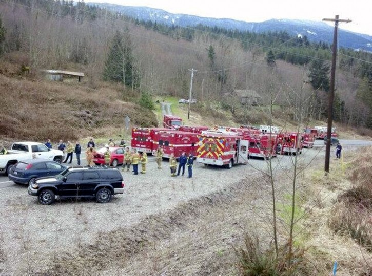 A handout image released by the Washington State Patrol shows emergency workers assisting at the scene of a mudslide which destroyed several homes and killed at least three people in Oso, Washington, USA, 22 March 2014.  EPA/WASHINGTON STATE PATROL