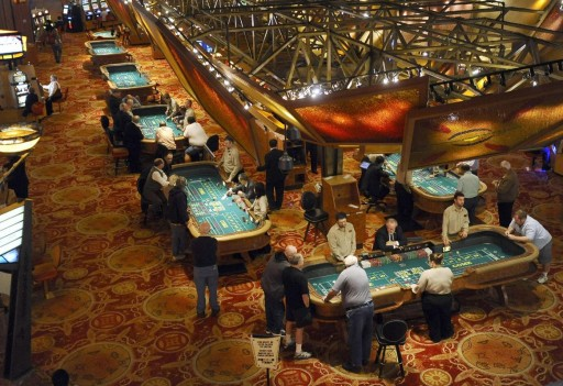 FILE - In this Sept. 18, 2013 casino file photo, patrons play craps at tables at Mohegan Sun in Uncasville, Conn. (AP Photo/Jessica Hill, File)