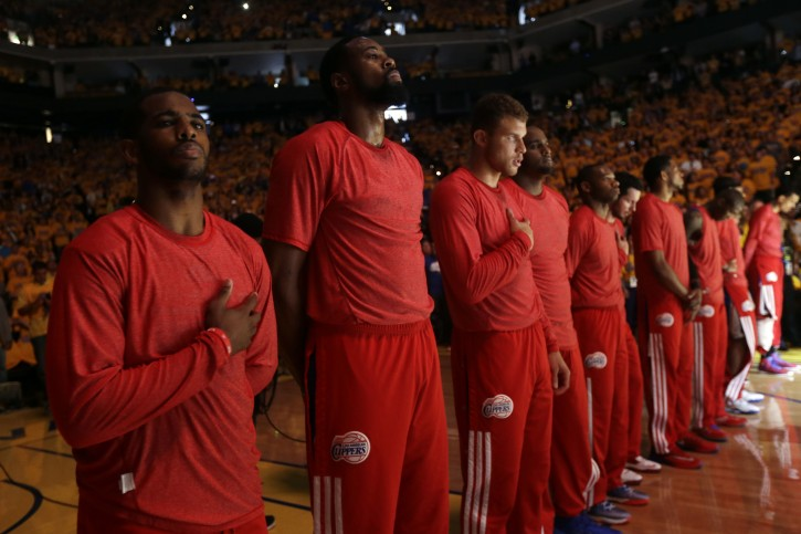 Members of the Los Angeles Clippers listen to the national anthem before Game 4 of an opening-round NBA basketball playoff series against the Golden State Warriors on Sunday, April 27, 2014, in Oakland, Calif. The Clippers chose not to speak publicly about owner Donald Sterling. Instead, they made a silent protest. The players wore their red Clippers' warmup shirts inside out to hide the team's logo. (AP Photo/Marcio Jose Sanchez)